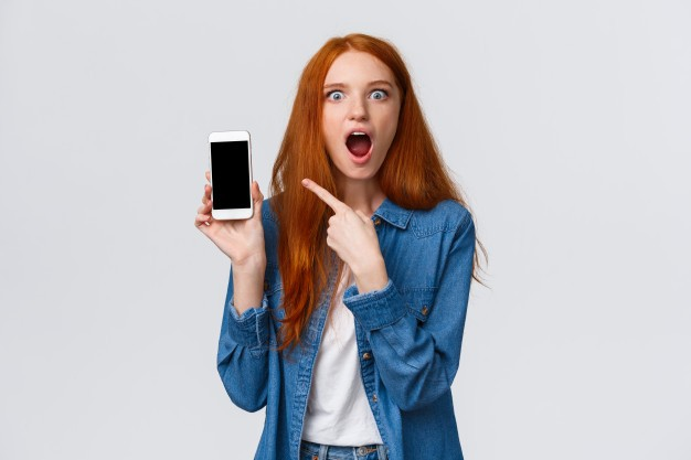 mujer-pelirroja-impresionada-apuntando-al-telefono-inteligente_1258-7505